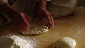 Preparing the dough. A hand held, close up shot of a person preparing the dough on a big wooden board stock video