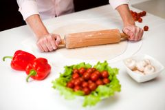 Preparing a dough for italian pizza close up. Chef is rolling dough for a italian pizza with pepperoni and mushrooms Stock Image