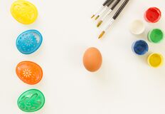 Preparing an Easter egg for painting. Paints. stencils and brushes on a white background. Place for text.