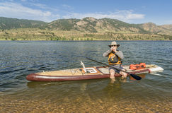 Preparing expedition stand up paddleboard for a trip. Fort Collins, CO, USA - August 2, 2017: A senior paddler eating energy food when taking a break from royalty free stock photography