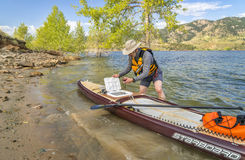 Preparing expedition stand up paddleboard for a trip. Fort Collins, CO, USA - August 2, 2017: A senior paddler is launching Starboard Expedition paddleboard with royalty free stock photos