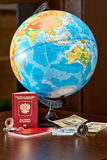 Preparing for the far journey: the choice of areas to relax. Globe, money, passport and compass are on the table Stock Photography