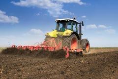 Preparing field for sowing. Worker is preparing field for sowing. Working with tractor Stock Photography