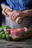 Preparing filet mignon - hands seasoning the steak. Wood background stock photos