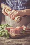 Preparing filet mignon - hands seasoning the steak. Wood background, toned royalty free stock images