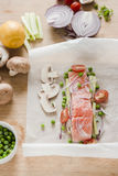 Preparing fish. Raw salmon fillet with other ingredients. Raw fresh salmon fillet with red onion slices, cherry tomato, garden peas, mushrooms and celery over Stock Photography