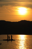 Preparing for fishing. Three people preparing their bait before fishing on sunset Royalty Free Stock Photo