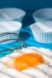 Preparing food. Cupcake holders, flour and egg (selective focus Stock Photo