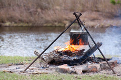 Preparing food on campfire. In wild camping on pond background Royalty Free Stock Photos