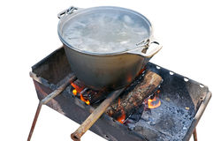 Preparing food on campfire. Outdoors cooked stew boiling on the fire Royalty Free Stock Image