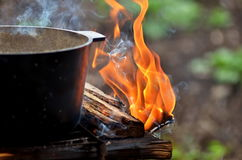 Preparing food on campfire. Outdoor summer. Fish soup cooking in a pot on a fire Royalty Free Stock Photography