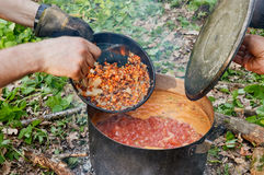 Preparing food on campfire. In wild camping. borscht, soup Royalty Free Stock Images