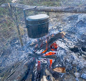 Preparing food on campfire in wild camping. Preparing food and hot pot on campfire in wild camping Stock Images