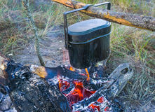Preparing food on campfire in wild camping. Preparing food and hot pot on campfire in wild camping Royalty Free Stock Images