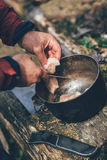 Preparing food on campfire in wild camping. Man cutting meat with a knife Royalty Free Stock Photo