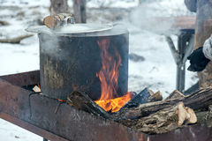 Preparing food on campfire in wild camping. Shurpa - soup with meat and potato on the fire Stock Photography