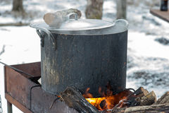 Preparing food on campfire in wild camping. Shurpa - soup with meat and potato on the fire Stock Images