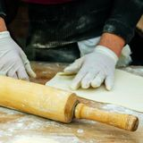 Preparing food. Human hands in gloves make dough products. Rolling pin for the dough next to it. Square. Close-up stock image
