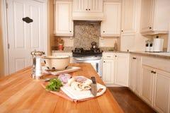 Preparing Food on Kitchen Island. Preparing vegetables on butcher block kitchen island royalty free stock images