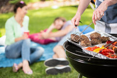 Preparing a food. Young people are preparing a food at the barbecue Royalty Free Stock Photography