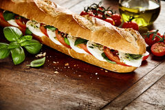 Preparing a fresh baguette with Caprese filling Stock Images