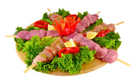 Preparing fresh beef steak shishkabobs. With vegetables ready for the grill. Isolated on white Stock Image