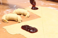 Preparing fresh croissants with jam Royalty Free Stock Image