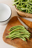 Preparing Fresh Homegrown Green Beans - Overhead V. Overhead view of fresh homegrown green beans shows several green beans on an aged wooden cutting board with a Stock Images