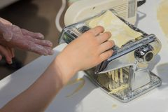 Preparing fresh homemade pasta, noodles with traditional rolled pasta machine, male cook hand and his student`s pupil. Preparing fresh homemade pasta, noodles Royalty Free Stock Images