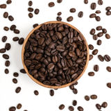 Preparing fresh roasted coffee beans in small wooden bowl on whi. Preparing fresh roasted coffee beans in wooden bowl on white background Stock Photo