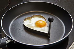 Preparing fried eggs in heart form Royalty Free Stock Photos