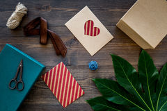 Preparing gift and greeting card. Gift boxes, card, envelope, ribbon dark wooden background top view Royalty Free Stock Photos