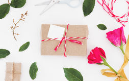 Preparing gift for valentines, gift box with blank card and roses with leaves, on white table Royalty Free Stock Images
