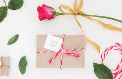Preparing gift for valentines, gift box and roses with leaves, on white table Royalty Free Stock Photo