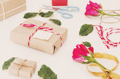 Preparing gift for valentines, gift box and roses with leaves, on white table Royalty Free Stock Image
