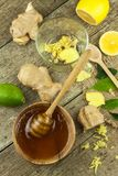 Preparing ginger tea against influenza. Traditional treatment for colds. Ginger, lemon and honey bowl on wooden table. Stock Images