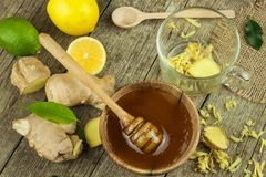 Preparing ginger tea against influenza. Traditional treatment for colds. Ginger, lemon and honey bowl on wooden table. Royalty Free Stock Photos
