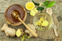 Preparing ginger tea against influenza. Traditional treatment for colds. Ginger, lemon and honey bowl on wooden table. Royalty Free Stock Images