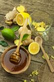 Preparing ginger tea against influenza. Traditional treatment for colds. Ginger, lemon and honey bowl on wooden table. Royalty Free Stock Photography