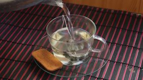 Preparing green tea in transparent teacup. With digestive biscuit on a side stock footage
