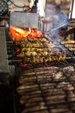Preparing grilled skewed meat on bbq in restaurant.  Royalty Free Stock Images
