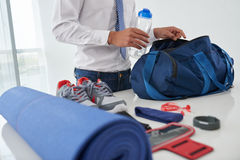 Preparing gym bag. Cropped image of businessman preparing gym bag at home Stock Photography