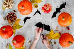 Preparing for halloween. Hands cut bats out of paper. Figures and pumpkins on grey background top view.  Royalty Free Stock Photos