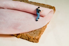 Preparing A Ham Sandwich. A miniature model workman rolls out a slice of ham on a slice of brown bread, back view with copyspace Stock Photography