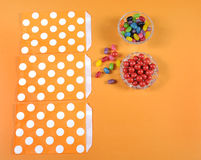 Preparing Happy Halloween candy trick or treat bags. On bright colorful modern orange background or childrens party favors Royalty Free Stock Photography