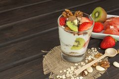 Preparing healthy breakfast for kids. Yogurt with oatmeal, fruit, nuts and chocolate. Oatmeal for breakfast. Preparing diet meals. Stock Image