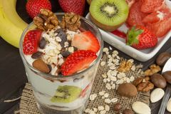 Preparing healthy breakfast for kids. Yogurt with oatmeal, fruit, nuts and chocolate. Oatmeal for breakfast. Preparing diet meals. Stock Images