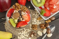 Preparing healthy breakfast for kids. Yogurt with oatmeal, fruit, nuts and chocolate. Oatmeal for breakfast. Preparing diet meals. Royalty Free Stock Image