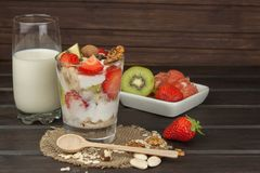 Preparing healthy breakfast for kids. Yogurt with oatmeal, fruit, nuts and chocolate. Oatmeal for breakfast. Preparing diet meals. A healthy diet for athletes stock photo