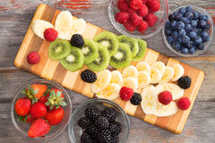 Preparing a healthy fruit salad with mixed berries Royalty Free Stock Image